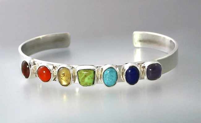a silver rainbow bracelet by jocelyn hunter jewelry that represents the chakras and lgbt+ community. The stones are garnet, gaspeite, amethyst, carnelian, citrine, turquoise, and lapis lazuli.